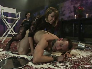 a dominatrix fucks two males with a strapon during a BDSM session
