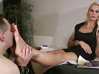 Platinum blonde tattooed mistress in black dress gets her feet worshiped by undisguised fat slave